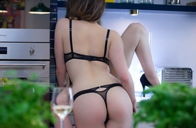 Lingerie wearing lesbians kiss in the kitchen