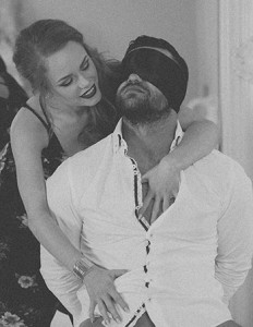 Man blindfold with girl gently caressing his body in soft erotic BDSM style
